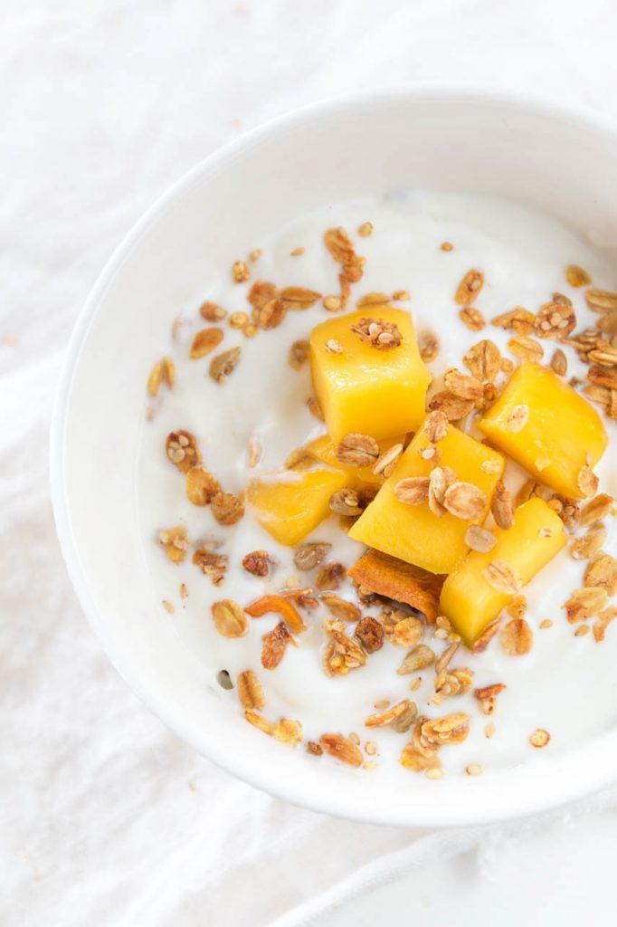 Knuspriges DIY Mango Granola selbst machen - das perfekte Müsli zum Frühstück mit wenig Zucker - noch leckerer schmeckt es mit Joghurt und frischer Mango