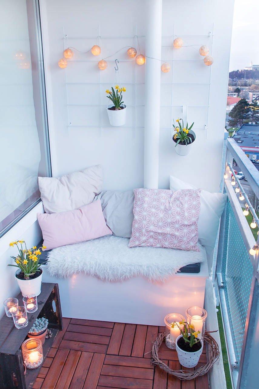 gemütlicher Balkon am Abend mit DIY Möbeln und Lichterketten