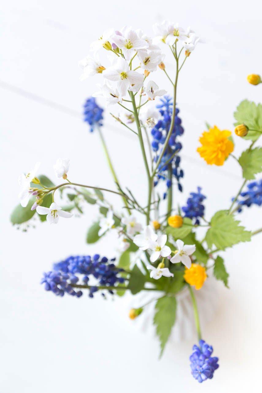 Frühlingsblumen mit Rapunzeln, Perlhyazinthen und weißen Blumen - die perfekte Frühlingsdeko für den Tisch
